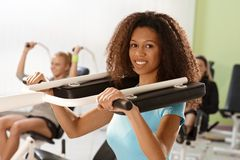 Beautiful afro woman training on weight machine Stock Photos