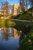 Beautiful afternoon light in park with old castle ruins. Beautiful afternoon light in public park with green grass and old castle ruins reflecting in the pond Royalty Free Stock Images