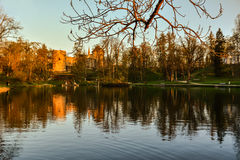 Beautiful afternoon light in park with old castle ruins. Beautiful afternoon light in public park with green grass and old castle ruins reflecting in the pond Royalty Free Stock Photography