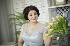 Beautiful aged asian woman. In silver dress sitting in spring studio stock photography