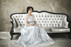 Beautiful aged asian woman. In silver dress sitting in spring studio stock photo