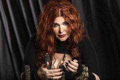 Beautiful aged redheaded woman fortune teller performs a magical ritual. Horizontal royalty free stock photography