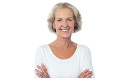 Beautiful aged woman with crossed arms. Aged woman with crossed arms isolated over white Stock Image