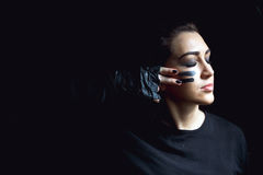 Beautiful aggressive woman over dark background. Dark and mysterious a pretty girl stands in shadow with camoflauge paint. On her face Stock Photo