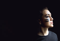 Beautiful aggressive woman over dark background. Dark and mysterious a pretty girl stands in shadow with camoflauge paint. On her face Stock Photography
