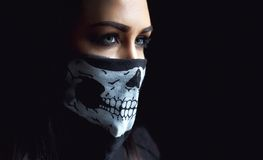 Beautiful aggressive woman over dark background. Dark and mysterious a pretty girl stands in shadow with camoflauge paint. On her face Royalty Free Stock Photography