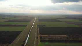 Agricultural fields with drainage canal - drone shot moving forward