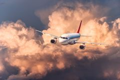 Beautiful airplane is flying in colorful clouds Stock Image
