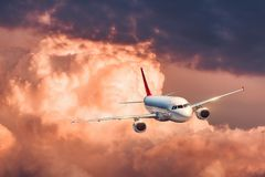 Beautiful airplane is flying in colorful clouds Stock Photo
