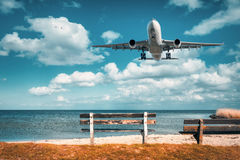 Beautiful airplane and wooden bench at the sea. Landscape with white passenger airplane is flying in the blue sky with clouds over sea in summer. Passenger Royalty Free Stock Photo