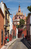 Beautiful Alley with Colorful Buildings Leading To Parroquia de San Miguel Arcangel church in Mexico Stock Images