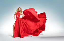 Beautiful alluring blond woman in red waving dress stock images