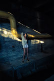 Beautiful alone girl and abandoned sewerage underground with ray of sunshine. Royalty Free Stock Photo