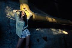 Beautiful alone girl and abandoned sewerage underground with ray of sunshine. Royalty Free Stock Photography