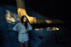 Beautiful alone girl and abandoned sewerage underground with ray of sunshine. Royalty Free Stock Image
