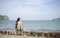Beautiful alone young asian woman at seashore near the beach.blurred sea and sky in background.selective focus.filtered image Royalty Free Stock Images