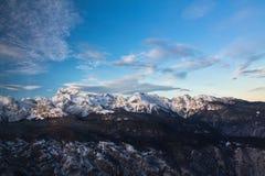 Beautiful alpine chain of snowy mountains of julian alps in sunset blue sky. Bohinj, slovenia Stock Photos