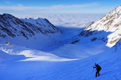 Beautiful alpine landscape with blue sky, sunshine and sea clouds in winter. Fagaras Mountains Stock Photos