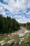 Beautiful alpine landscape, mountains scenery, sky blue clouds. Travel background. Summer panoramic view. Mountain hiking. Forest. River landscape. River royalty free stock photo