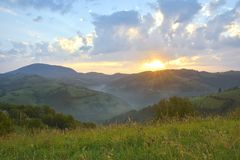 The Beautiful alpine meadow with green grass. sunrise. landscape on wild transylvania hills. Holbav. Romania. Low key, dark backgr Royalty Free Stock Images