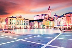 Beautiful amazing city scenery in the central square with the old clock tower in Piran, the tourist center of Slovenia in the. Light of lanterns. popular stock photography