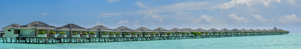 Beautiful amazing panorama of the water bungalows at the tropical island at Maldives. Beautiful amazing panorama of the water bungalows located at the tropical Stock Photos