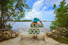 Beautiful amazing view of a woman sitting and relaxing on the bench in tropical garden near the water Royalty Free Stock Photos