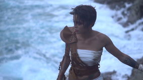 Beautiful amazon woman warrior. Wearing white outfit and brown leather swordbelts climbing on the rocks with rifle over stormy sea background - video in slow stock footage