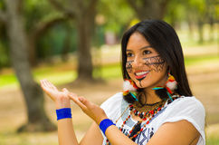 Beautiful Amazonian woman with indigenous facial paint and white traditional dress posing happily for camera Stock Images