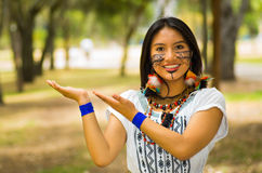 Beautiful Amazonian woman with indigenous facial paint and white traditional dress posing happily for camera Stock Photography