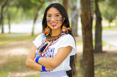 Beautiful Amazonian woman with indigenous facial paint and white traditional dress posing happily for camera in park Stock Photos