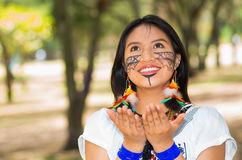 Beautiful Amazonian woman with indigenous facial paint and white traditional dress posing happily for camera in park Royalty Free Stock Images
