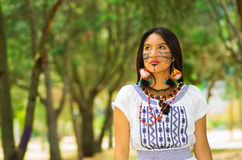 Beautiful Amazonian woman with indigenous facial paint and white traditional dress posing happily for camera in park Royalty Free Stock Photo