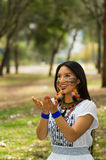 Beautiful Amazonian woman with indigenous facial paint and white traditional dress posing happily for camera in park Stock Photography