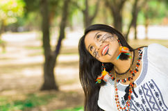 Beautiful Amazonian woman with indigenous facial paint and white traditional dress posing happily for camera in park. Environment, forest background Royalty Free Stock Photo