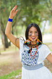 Beautiful Amazonian woman with indigenous facial paint and white traditional dress posing happily for camera in park Stock Image