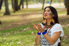 Beautiful Amazonian woman with indigenous facial paint and white traditional dress posing happily for camera in park. Environment, forest background Stock Images