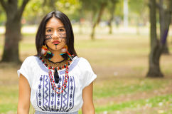 Beautiful Amazonian woman with indigenous facial paint and white traditional dress posing serious expression for camera Royalty Free Stock Images