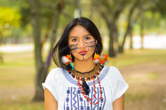 Beautiful Amazonian woman with indigenous facial paint and white traditional dress posing serious expression for camera Stock Photo
