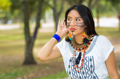 Beautiful Amazonian woman with indigenous facial paint and white traditional dress posing serious expression for camera Royalty Free Stock Photography