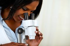Beautiful american black woman with a microscope. Portrait of a beautiful afro-american black woman using a microscope at soft colors composition Royalty Free Stock Photography