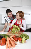 Beautiful American couple working at home kitchen in apron mixing vegetable salad smiling happy Stock Photography