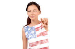 Beautiful American girl pointing in front to you. Attractive girl with USA flag on her blouse. Isolated on white. Blur on the model, focus on the hand Royalty Free Stock Photos