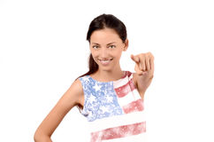Beautiful American girl pointing in front to you. Attractive girl with USA flag on her blouse. Isolated on white. Focus on the model, blur on the hand Royalty Free Stock Image