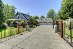 Beautiful american house with iron gates. View of open entrance iron gates and driveway Stock Image