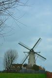Beautiful ancient flemish windmill. Beautiful ancient white flemish windmill in a bluish clouded sky Stock Image