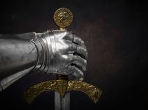 A beautiful ancient sword of the Order of the Knights Templar an. D an iron knight`s glove on a dark beautiful background Royalty Free Stock Images