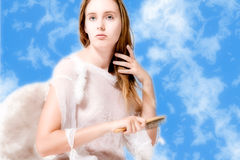 Beautiful angel in the clouds doing her hair Royalty Free Stock Photography