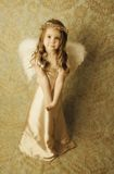 Beautiful angel girl. Beautiful young girl wearing angel wings and gold halo wreath with soft sweet smile expression, vintage look Royalty Free Stock Images