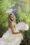 Beautiful angel girl in forest. Beautiful angel girl with magic fan in forest Stock Photo